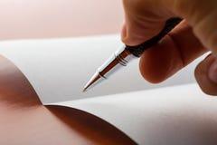 在纸的人的手文字由圆珠笔 免版税库存照片