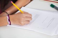 在纸的女小学生文字在书桌 免版税图库摄影