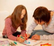 在纸的妈妈和女儿绘画 免版税库存照片