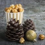 在纸的开胃金黄焦糖玉米花镶边了在新年` s内部与冷杉球果,金黄新年的` s的杯子 免版税库存图片