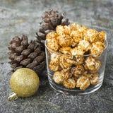 在纸的开胃金黄焦糖玉米花镶边了在新年` s内部与冷杉球果,金黄新年的` s的杯子 图库摄影