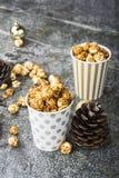 在纸的开胃金黄焦糖玉米花镶边了在新年` s内部与冷杉球果,金黄新年的` s的杯子 免版税库存照片