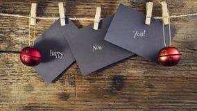 在纸的新年好与晒衣夹,垂悬在木背景的一条绳索 与新年快乐的贺卡 免版税库存图片