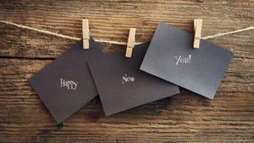 在纸的新年好与晒衣夹,垂悬在木背景的一条绳索 与新年快乐的贺卡 库存图片