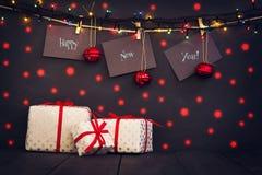 在纸的新年好与晒衣夹,垂悬在黑暗的木背景的一条绳索 与一愉快新的贺卡 免版税图库摄影