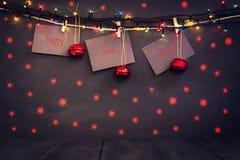 在纸的新年好与晒衣夹,垂悬在黑暗的木背景的一条绳索 与一愉快新的贺卡 免版税库存图片