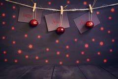 在纸的新年好与晒衣夹,垂悬在黑暗的木背景的一条绳索 与一愉快新的贺卡 库存照片