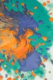 在纸的溢出的明亮的橙色和深蓝油漆 免版税图库摄影