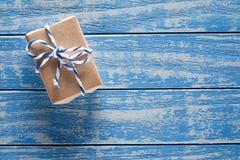 在纸的礼物盒在一张蓝色木桌上 免版税库存照片
