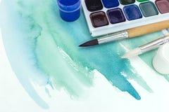在纸的绿色水彩绘画与油漆和油漆刷 库存照片