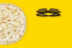 在纸盒碗和3d戏院玻璃的玉米花在与空间的黄色背景文本顶视图的,明亮的夏天概念 免版税库存图片