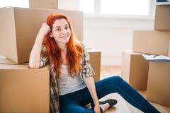在纸盒箱子中的愉快的妇女,新的家 免版税库存图片