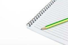 在纸笔记本上把放的铅笔 免版税图库摄影