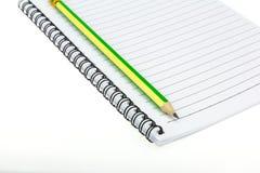 在纸笔记本上把放的铅笔 库存图片