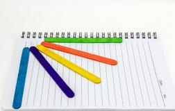 在纸笔记本的五颜六色的木冰淇凌棍子 免版税图库摄影