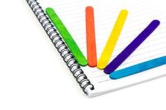 在纸笔记本的五颜六色的木冰淇凌棍子 免版税库存照片