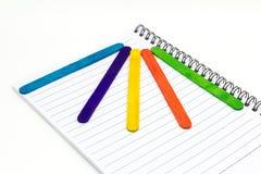 在纸笔记本的五颜六色的木冰淇凌棍子 库存照片
