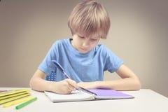 在纸笔记本的男孩文字 做他的家庭作业锻炼的男孩 免版税库存图片