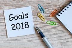在纸笔记背景和办公室suplies的2018个目标在木桌、企业和新年概念 库存图片