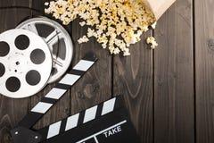 在纸箱和电影拍板在桌上,电影放映时间概念的玉米花 库存照片