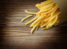 在纸篮子的炸薯条在木背景 免版税图库摄影