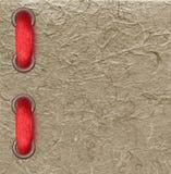 在纸纹理的红色丝带 免版税库存照片