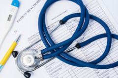 在纸耐心健康历史医疗查询表形式谎言医生诊断器械上-听诊器和温度计 i的过程 免版税库存照片