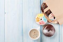 在纸袋和咖啡杯的五颜六色的油炸圈饼 免版税库存图片