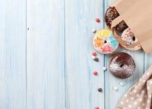 在纸袋的五颜六色的油炸圈饼 库存照片