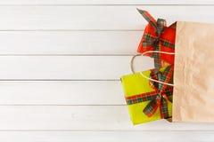 在纸袋的传统圣诞节礼物在白色土气木桌背景 免版税库存图片