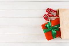 在纸袋的传统圣诞节礼物在白色土气木桌背景 免版税库存照片
