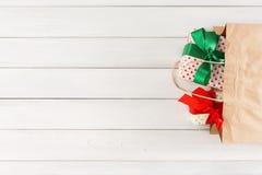 在纸袋的传统圣诞节礼物在白色土气木桌背景 库存照片