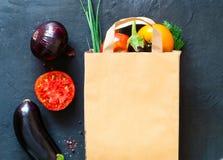 在纸袋的传统菜在黑暗的背景,购物在超级市场,健康饮食,拷贝空间的概念 免版税库存照片