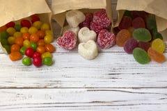 在纸袋的甜点 多彩多姿的糖果,以心脏的形式橘子果酱 免版税库存照片