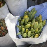 在纸袋的Unblown郁金香在铝桶的待售在花店旁边 免版税库存图片