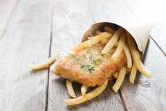 在纸锥体包裹的炸鱼加炸土豆片 图库摄影