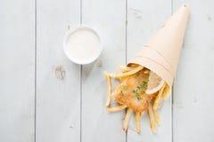 在纸锥体包裹的顶视图炸鱼加炸土豆片 免版税图库摄影