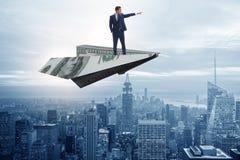 在纸飞机上的商人飞行在企业概念 免版税库存照片