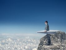 在纸飞机上的商人飞行 图库摄影