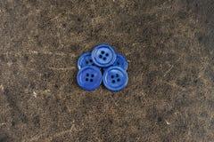 在纹理桌上的蓝色按钮 库存照片