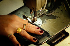 在纺织品工厂剪裁工作在一台缝纫机 库存图片