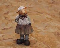 在纺织品背景的陶瓷绵羊小雕象 免版税库存照片