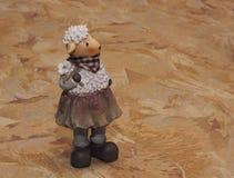 在纺织品背景的陶瓷绵羊小雕象 库存图片
