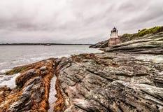 在纽波特,罗德岛州防御小山灯塔,位于在剧烈的岩石海岸线 免版税图库摄影