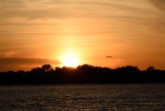 在纽瓦克机场的一次商业喷气机着陆与背景的金黄日落 免版税图库摄影