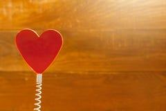 在线圈弹簧的红心 背景土气木 圣徒情人节,爱卡片,横幅,消息概念 免版税库存图片