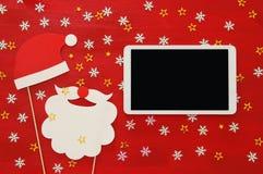 在线圣诞节假日购物概念 圣诞老人红色和胡子帽子在片剂设备旁边 库存照片