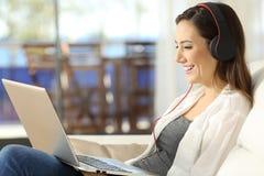 在线的女性观看的媒介在膝上型计算机 图库摄影