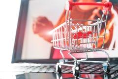 在线购物概念 在膝上型计算机的购物车台车有拿着信用卡背景的女孩的 库存照片