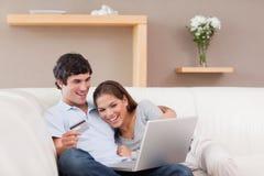 在线购物的沙发的夫妇 免版税库存照片
